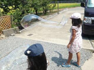 針金ハンガーのシャボン玉で遊ぶ子供